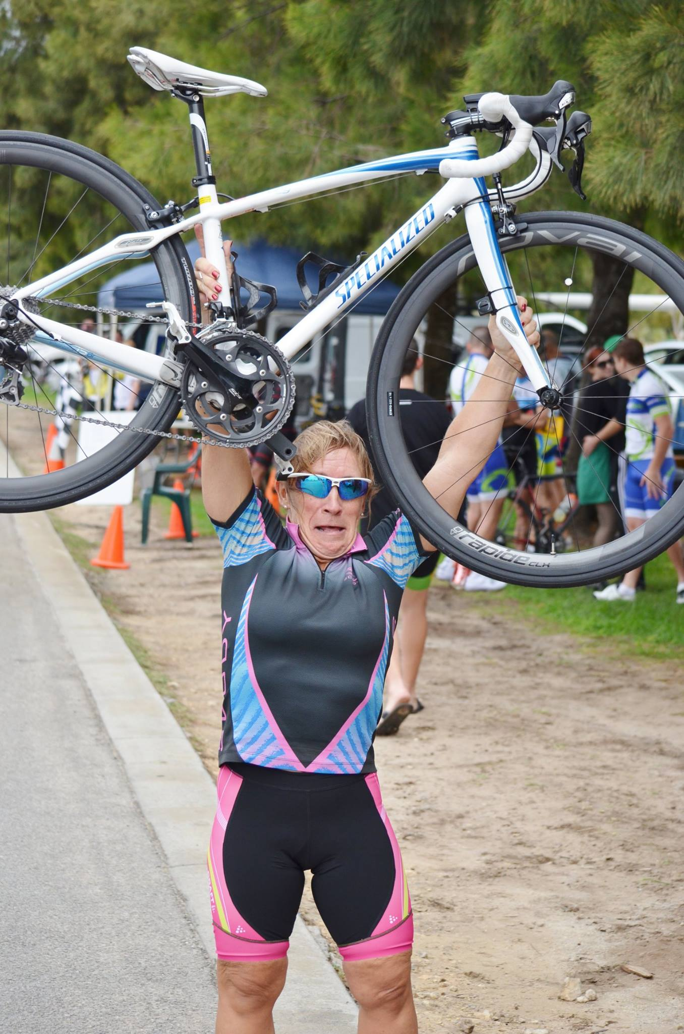 zoe stalton hold bicycle aloft after winning