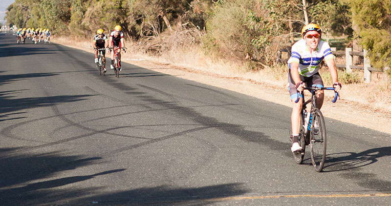 Peter Clark winning B grade ahead of his two breakaway companions with the bunch in the distance