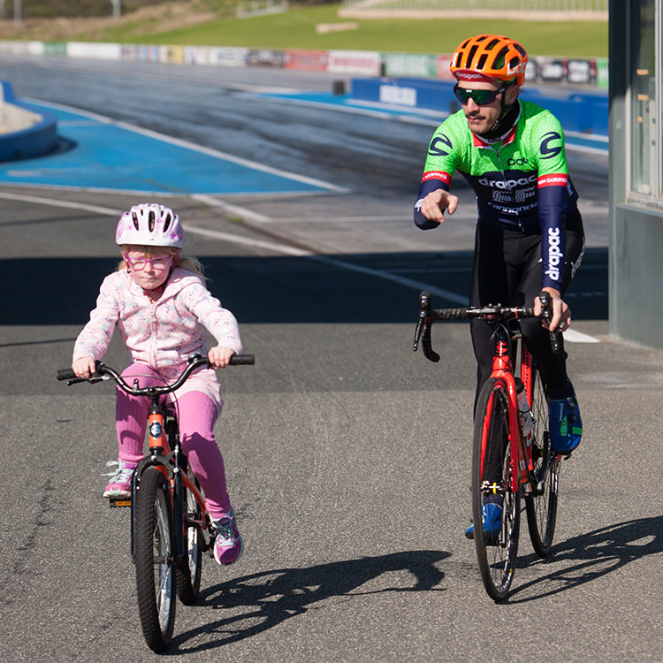Young girl on bicycle with pro rider
