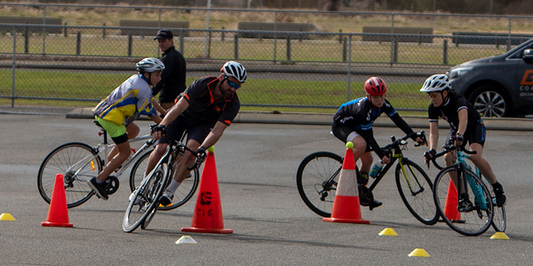 adult and three junior cyclists practising cornering around cones